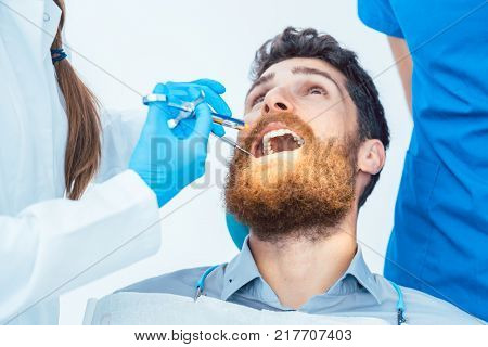 Low-angle close-up view of a man with the mouth open during a medical procedure in the dental office of an experienced female dentist