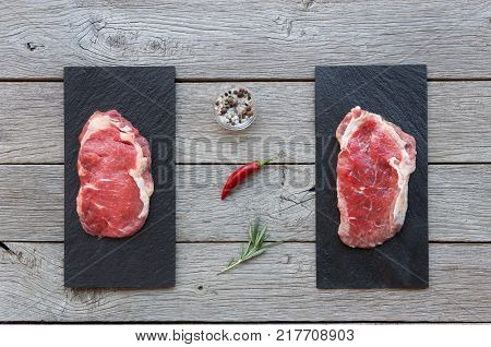 Raw beef steaks on dark wooden table background, top view. Fresh juicy meat with rosemary on stone boards. Cooking ingredients, butcher's and grocery concept
