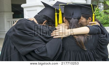 people with black gowns hug neck in grouping
