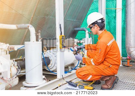 Electrician operator inspect and checking heating ventilated and air conditioning (HVAC) air conditioning service in offshore oil rig platform while worker charging refrigerant in system.
