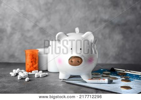 Piggy bank with medicines on grey table. Health care concept