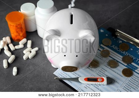 Piggy bank with medicines on grey background. Health care concept