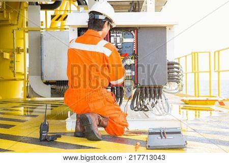 Electrical and instrument worker inspect and checking voltage and current of electric system at oil and gas platform for preventive maintenance offshore oil rig electrician occupation.