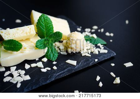 Heap of aerated porous white chocolate bars with green mint leaves on dark slate board on black background. Tasty bubble milk chocolate bar. Selective focus closeup.