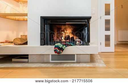 Woollen socks by the Christmas fireplace. Wool socks at a modern Christmas fireplace. Close up on feet. Winter and Christmas holidays concept.