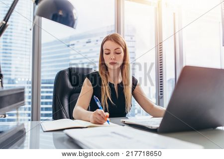 Female chief executive sitting at her desk taking notes in datebook writing with pen and using her computer in modern office building.