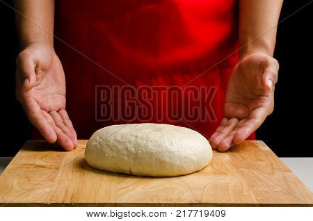 Bread cooking, kneading bread dough by hand on wooden board, homemade bakery