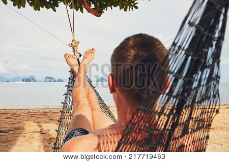 Young man (tourist) relaxing in the hammock on the sand beach - selective focus on foot. Koh Yao Noi island situated between Phuket and Krabi in Thailand.