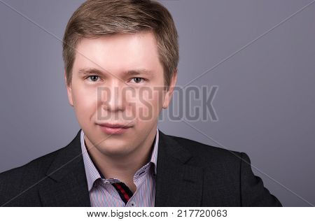 Horizontal closeup portrait young handsome man in jacket and shirt. Neutral grey background