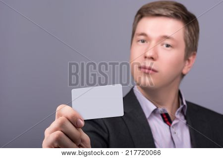 Horizontal closeup portrait of young attractive man in a jacket and shirt showing your business card or any other card. Neutral grey background