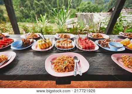 Lunch in the middle of the jungle. The table full of foods and fruits. Traditioal Pad Thai spring rolls melon and pineapple. Chiang Mai Province Thailand.
