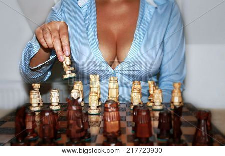 Some woman with a big neckline without face plays chess. Love game female weapons concept. Gender feminism seduction theme or other topic.