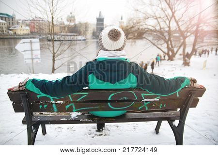 girl sitting on bench on waterfront in prague czech republic