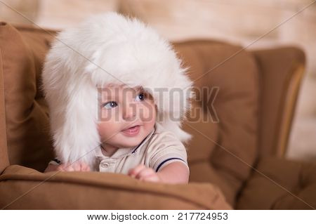 Happy Newborn Child Baby Boy With Pink Cheeks Posing On Hege Retro Casual Style Brown Couch Divan So