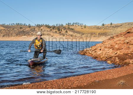 senior male paddler on stand up paddleboard, Horsetooth Reservoir with low water level in December