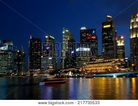 Skyscrapers from Merlion Park. Singapore, Asia - June 05, 2016 Office buildings, hotels, banks and Merlion, the national symbol of Singapore spurting water in the evening scenery of Merlion Park in Singapore ..
