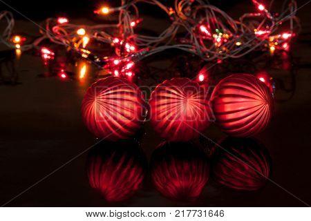 Three red christmas balls are lying on a mirror flooring. Christmas holidays.