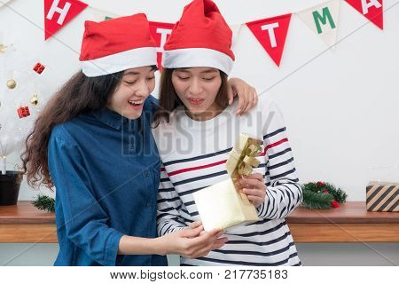 Two asia woman surprise when open gold gift box at holiday party with decoration flag at background giving Christmas party presentwow feeling and happiness momen tlesbian lgbt couple lifestyle