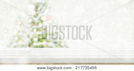 Empty white wooden table top with abstract muted blur christmas tree and snow fall background with bokeh lightHoliday backdropMock up banner for display or montage of product.