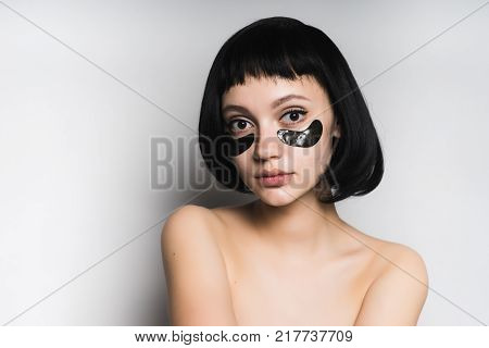 young beautiful girl with black hair looks, under the eyes black silicone patches