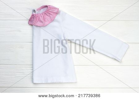 Girl's pajama folded in half. White cotton jacket with pink ruffle collar. Cute and cozy sleepwear for children.