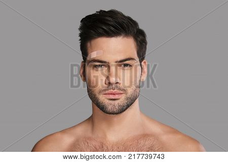 Little injury. Handsome young man with adhesive bandage above eyebrow looking at camera while standing against grey background