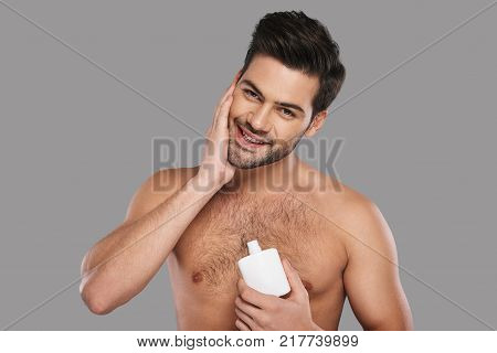 Feeling so fresh. Handsome young man applying aftershave lotion and smiling while standing against grey background