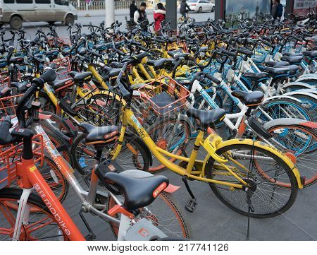 Wuhan Hubei China, 10 December 2017: Lots of bike sharing of several brands closeup with company logo of Mobike Hellobike and Ofo