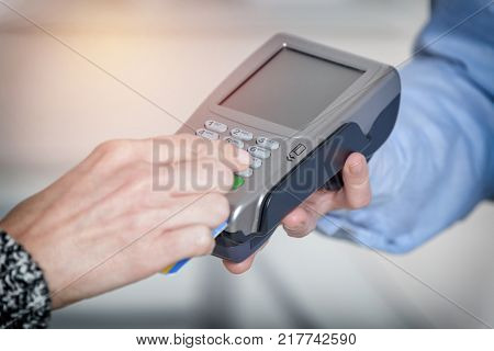 Entering PIN code on wireless payment terminal with inserted redit or debit card