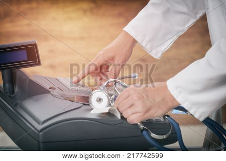 pharmacist or medical doctor holdnig stethoscope and using cash register at pharmacy or surgery