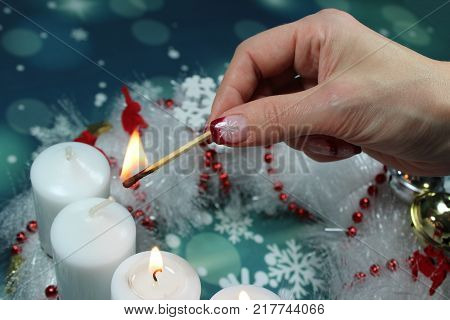 Third Advent Sunday/candles on an advent wreath/ A woman fires the third candle on an advent wreath.