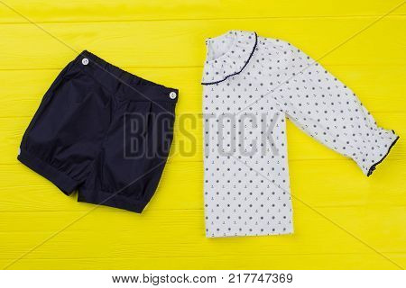 Shorts and jacket set on yellow background. Navy and white, sailor pattern. Kids clothes for comfy night rest.