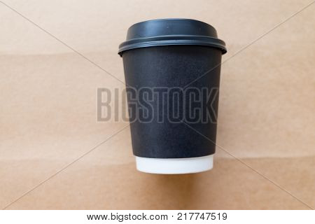Disposable black plastic cup with a lid on brown background