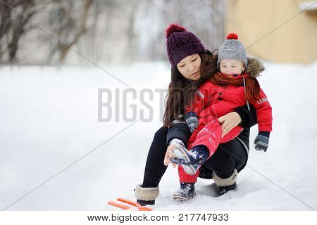 Young asian woman helping caucasian toddler boy with his winter clothing. Babysitting/childcarer concept. poster
