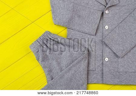 Gray pajama set on yellow. Combination of cotton shirt and pants. Comfy nightwear for good sleeping.