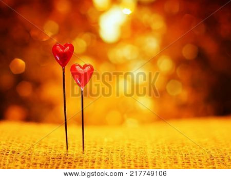 two sharp pins in the form of red hearts stuck in the burlap on the background of Golden holiday bokeh