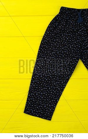 Fashionable floral pants on yellow background. Black loose garment with elastic waistband. Bright shot of girls apparel item.