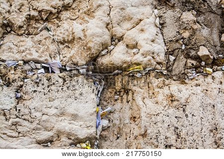 The Western Wall Jerusalem. Limestone and notes with prayers to the God. Traditions of the Jews. Close-up dark style photo.