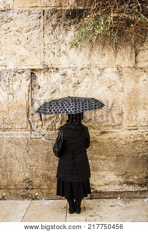 A lonely woman stands and prays before the western wall Jerusalem Israel. Rainy day. Traditions of Judaism.
