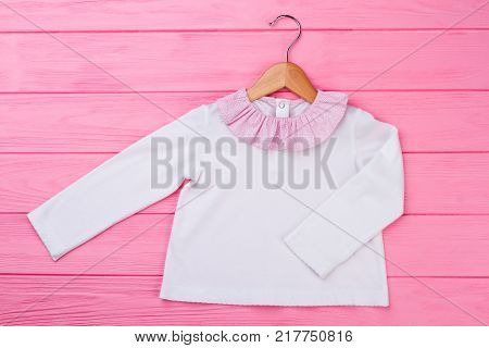 Pajama top for little girl. White garment with pink ruffle collar on wooden hanger. Sleeping apparel item.