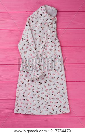 Cotton nightie with floral design. Ruffle cuffs and rounded collar. Sleepwear collection item on pink wooden display.
