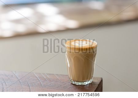 A Cup of Piccolo latte coffee with latte art on the wooden table background.