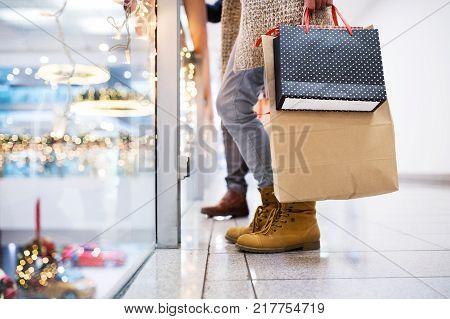 Unrecognizable senior couple doing Christmas shopping. Shopping center at Christmas time.