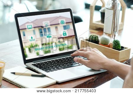 Man hands typing laptop computer with smart home control on screen device technology and lifestyle concept