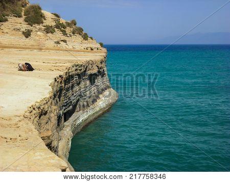 Sidari Corfu Greece - rocky cliff with backpacks and beautiful turquoise water