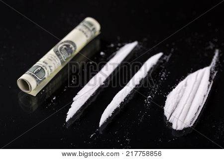 Rolled hundred dollars banknote and two lines of cocaine on black background, closeup