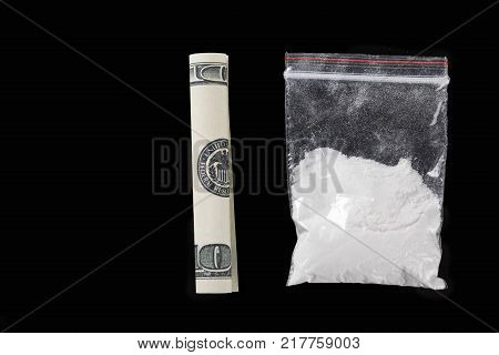 Rolled hundred dollars banknote and plastic bag of cocaine on black background, closeup
