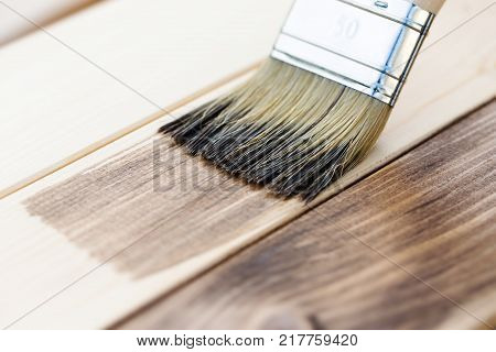Applying wood stain on wooden board, painting process of repair, macro shot.