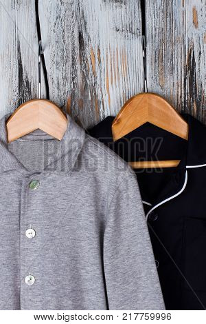 Gray and black pajama shirts on wooden hangers. Snuggly fit and comfy for sleep. Boy's wardrobe, PJs and sleepwear.