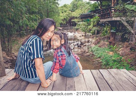Portrait woman and children smilling and sitting on wooden bridge with water stream of river in the background in vintage style.